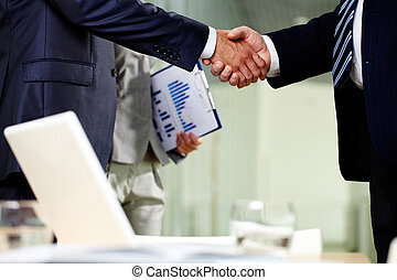 Contract of cooperation - Close-up of two men handshaking...