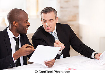 Contract on good conditions. Two cheerful business people in formalwear discussing something and pointing a paper