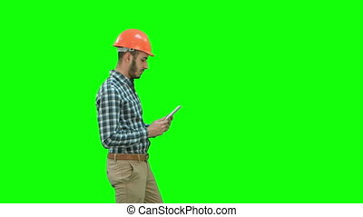 Contractor engineer in hardhat inspecting construction site holding digital tablet on a Green Screen, Chroma Key.