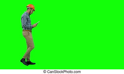 Contractor engineer inspecting construction site holding digital tablet on a Green Screen, Chroma Key.