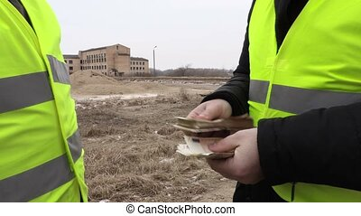 Contractor give euro banknotes to construction worker