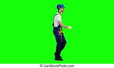 Contractor goes to the object with a helmet and tools. Green screen. Side view