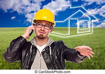 Contractor in Hard Hat on Cell Phone in Front of Ghosted House, Grass Field and Blue Sky with Clouds.