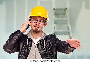 Contractor in Hard Hat on Cell Phone In Unfinished House