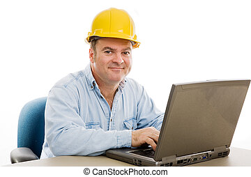 Friendly contractor in his office reviewing the plans on his computer. Isolated on white.