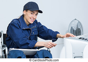 Contractor in wheelchair repairing electrical appliance