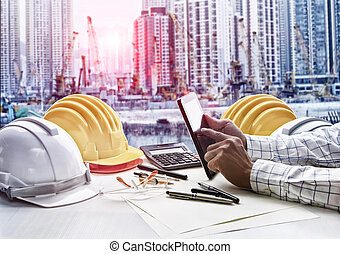 contractor man working on office table against construction site project