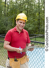 smiling handsome contractor repairman writing job estimate at suburban house with swimming pool