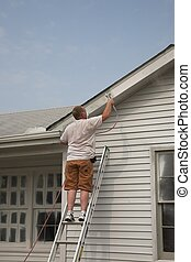 Contractor spraying house - Painter painting exterior of...
