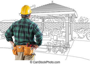 Contractor Standing Looking At Patio Pergola Design Drawing.