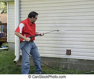 Contractor Using A Pressure Washer To Clean Vinyl Siding - ...