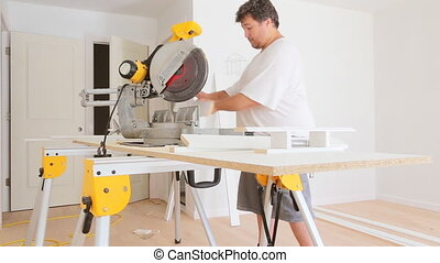 Contractor Using Circular Saw Cutting New Baseboard for...