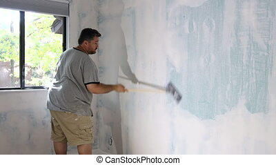 Contractor using sand trowel sanding the drywall with ...