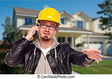 Contractor Wearing Hard Hat on Phone In Front of House
