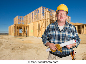 Contractor with Plans and Hard Hat In Front of New House Framing at Construction Site.