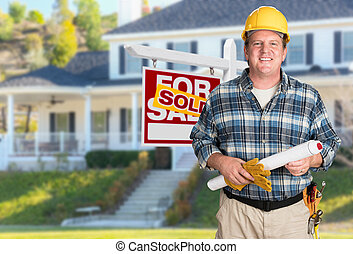 Contractor With Plans and Hard Hat In Front of Sold For Sale Real Estate Sign and House.