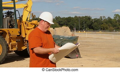 Contractor With Prints - Contractor holding blueprints at an...