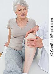 contrarié, femme aînée, obtenir, elle, genou, examiné