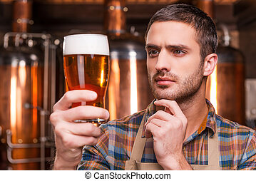 Controlling beer quality. Thoughtful young male brewer in ...