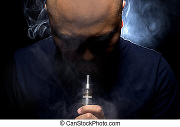 Controversial Vaping - Man with concealed identity smoking a...