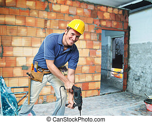 young handyman at work with drill in construction site