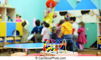 conundrum toy standing on table, in defocus clown blow bubbles for children