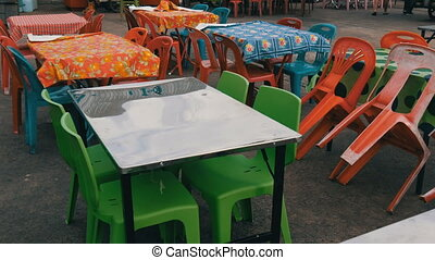 Conventional plastic tables and chairs in one of the...
