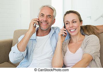 conversa par, seu, sofá, telefones, sentando, feliz