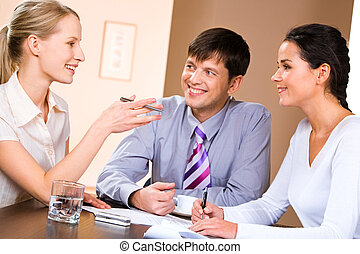 Conversation - Business people gathered together around the...