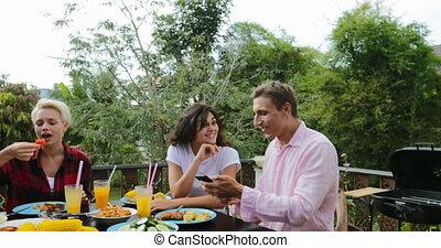 conversation, manger, gens, photo, prendre, séance, amis, jeune, téléphone portable, sourire, terrasse, dehors, groupe, heureux, table, intelligent, homme