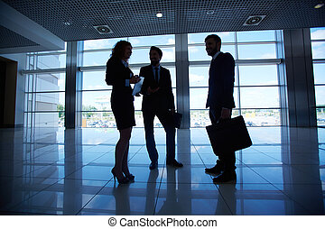 Conversation of co-workers - Silhouettes of three co-workers...