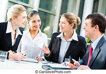 Conversation - Four business people sitting at the table and...