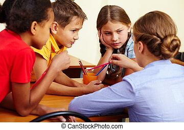 Portrait of smart schoolchildren and their teacher interacting in classroom
