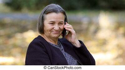 conversation, smartphone, personne âgée femme, dehors