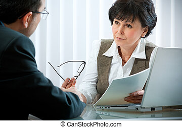 conversation - mid-adult businessman in a conversation with...