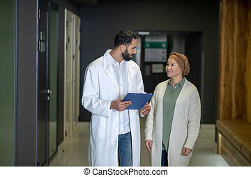 Tall male young doctor explaining diagnosis to the patient