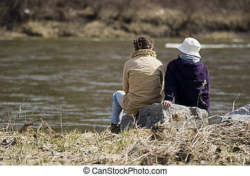 conversation - two people conversing at a river bank