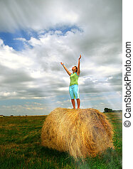 Conversation With God - A young woman on straw bale in...