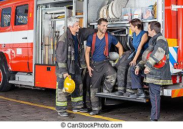 conversing, firefighters, firetruck