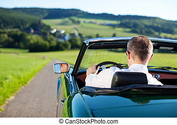Convertible car - Rear view shot of man driving a...