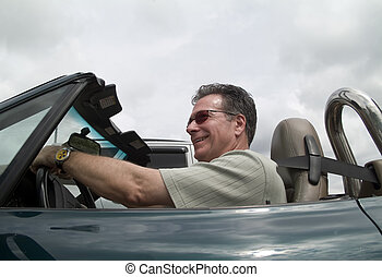 A man enjoying driving his convertible sports car with the top down.