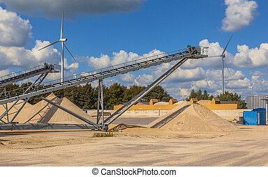 Conveyor belt on a Sand sorting site under blue clouded sky