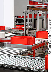Conveyor belt rollers - Red crates at conveyor rollers in...