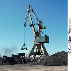Conveyor belt with charcoal and a crane in the background with blue sky