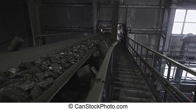 Conveyor belt with coal shooting in slow motion. There is...