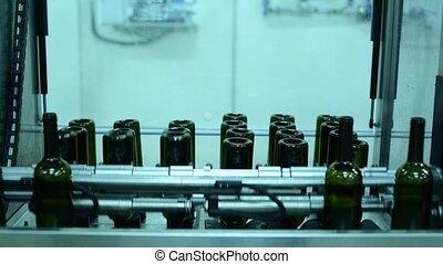conveyor with wine bottles at wine factory white wine production, bottle washing