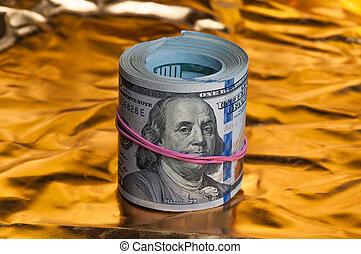 Convolution of American dollars. One hundred dollars in bills. On a golden background.