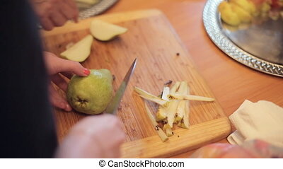 Cook chops on a wooden board ripe pear for the banquet