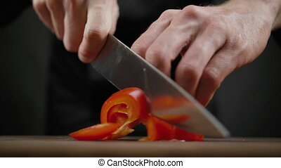 Cook chops red pepper on the wooden table on the black...