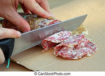 Cook cut the genuine salami